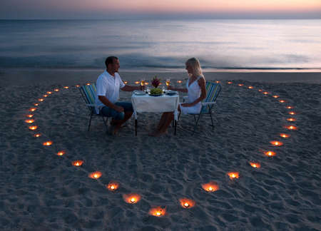A young couple share a romantic dinner with candles heart on the sea sand beach Foto de archivo