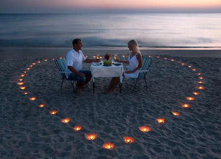 parejas romanticas: Una joven pareja compartir una cena romántica con velas en el corazón de la playa de arena de mar