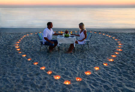 A young lovers couple share a romantic dinner with candles heart on the sea sand beach 写真素材