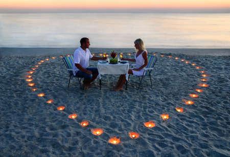 bougie coeur: Un jeune couple d'amoureux partager un dîner romantique avec des bougies coeur sur la plage de sable de la mer Banque d'images