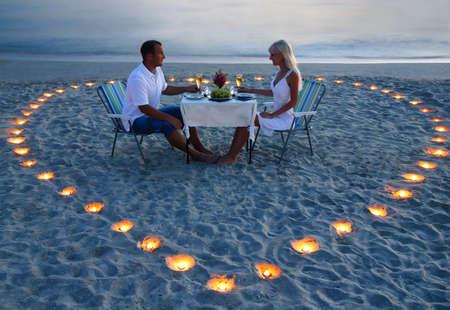 Una joven pareja de amantes compartir una cena romántica con velas corazón en la playa de arena de mar