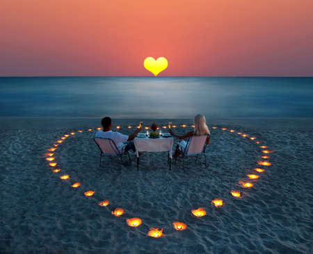 proposal: A young couple share a romantic dinner with candles heart on the sea sand beach Stock Photo