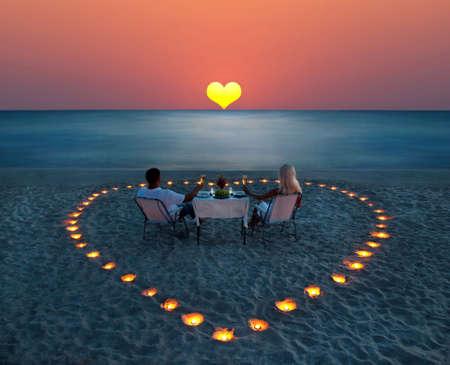 diner romantique: Une part jeune couple un dîner romantique avec bougies coeur sur la plage de sable de la mer