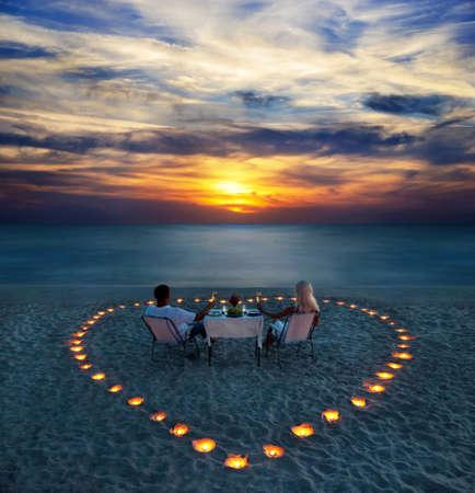 lãng mạn: Một cặp vợ chồng trẻ chia sẻ một bữa ăn tối lãng mạn với nến trái tim trên bãi biển cát biển