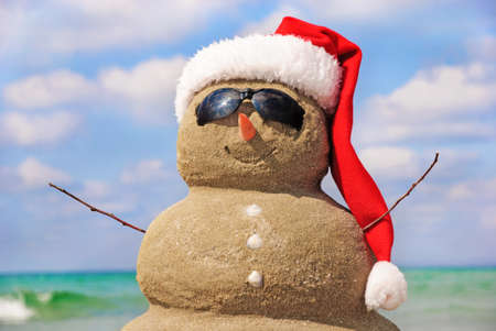christmas in july: Snowman made out of sand against the sky. Holiday concept can be used for New Year and Christmas Cards