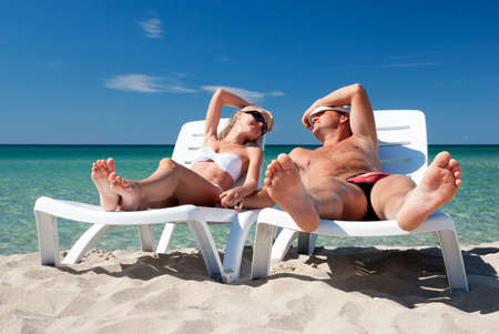 sea bed: Young couple sunbathe on the beach bed on the sea beach