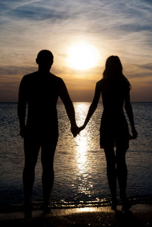 Young couple silhouette  on a sea beach holding hands and looking at sunset under the sea Stock Photo