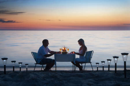A young couple share a romantic dinner with candles and wine glasses on the sea sand beach