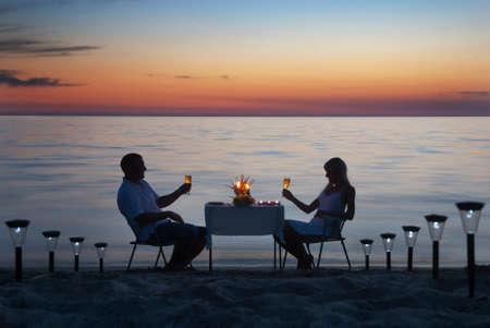 젊은 부부는 낭만적 인 저녁 식사를 촛불과 와인 잔으로 바다 모래 해변에서 공유합니다.