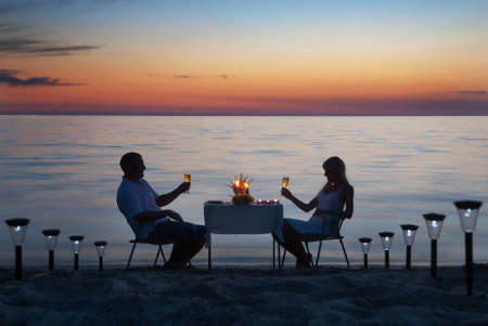 candle dinner: A young couple share a romantic dinner with candles and wine glasses on the sea sand beach