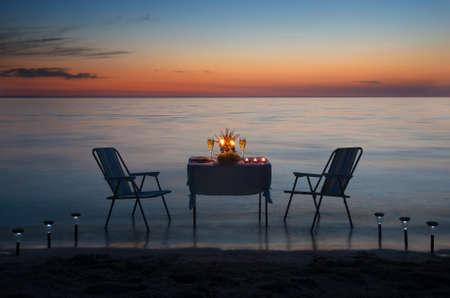 촛불과 와인과 함께 바다 해변에서 낭만적 인 저녁 식사