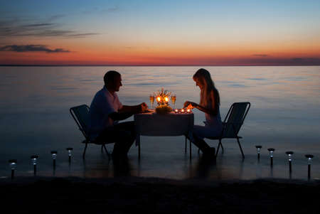A young couple share a romantic dinner with candles on the sea sand beach