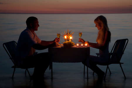 diner romantique: Un jeune couple part un d�ner romantique avec des bougies sur la plage de sable de la mer