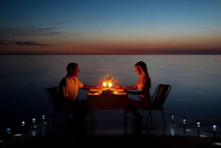 luna de miel: Una joven pareja compartir una cena romántica con velas en la playa de arena de mar