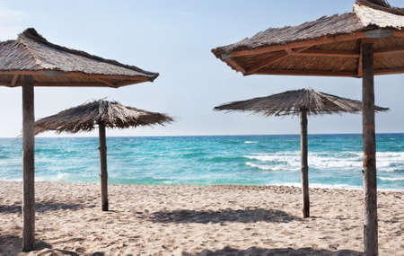 thatched: tropical sea beach with the  straw beach umbrellas