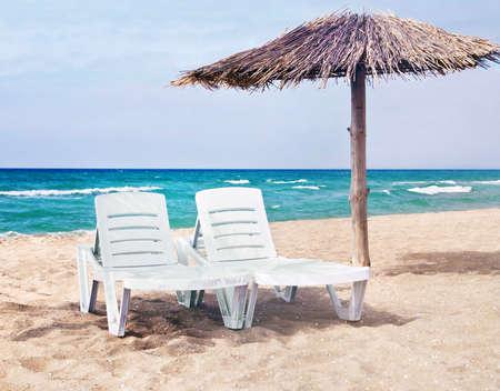sun umbrella: sea beach with the two beach beds and the beach umbrella
