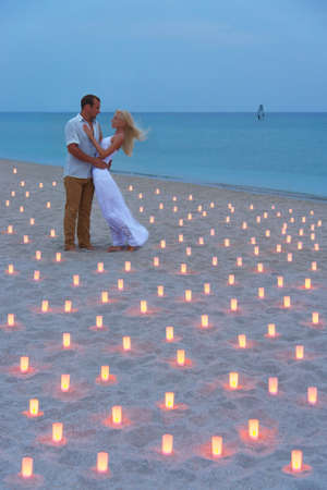 A man propose marriage to woman at sea beach in many candle lights against sunset- St.Valentines Day romantic concept