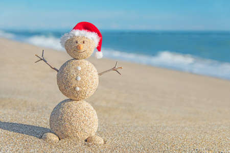 beach happy new year: Smiley sandy snowman in red santa hat. Holiday concept for New Years and Christmas Cards.