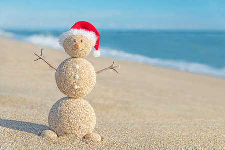 Smiley sandy snowman in red santa hat. Holiday concept for New Years and Christmas Cards.