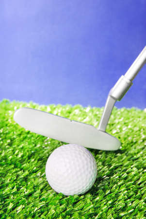 Golf ball and club on green field grass against blue sky - vertical image photo