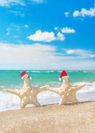 바다 모래 해변에서 산책 빨간 산타 모자에 바다 - 별 커플. 새 년 하루 크리스마스 휴가 개념.
