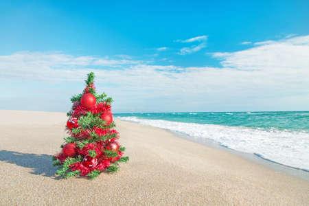 beach resort: �rbol de Navidad con adornos de color rojo en la playa del mar. Concepto de las vacaciones de Navidad.