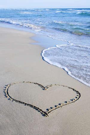 바다 파도에 대하여 젖은 해변 모래에 심장 개요 스톡 콘텐츠