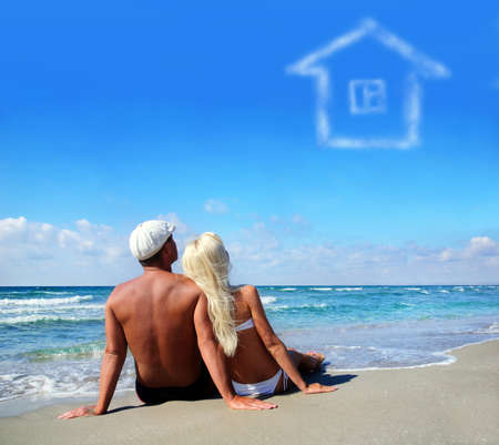 young couple on sea sand beach dreaming about the own home concept photo