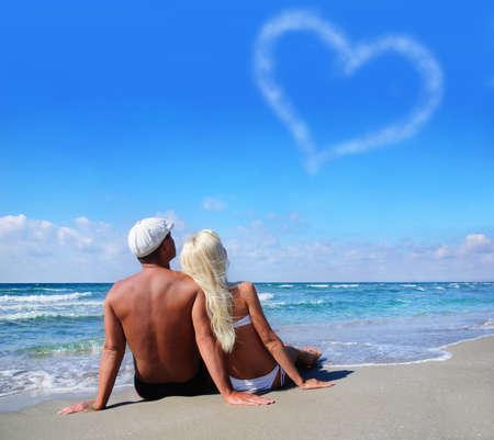 개념을 사랑 - 바다 모래 해변에서 젊은 부부는 하늘 흐린 마음을보고 스톡 콘텐츠