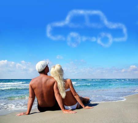 자신의 자동차 개념에 대해 꿈을 꾸고 바다 모래 해변에서 젊은 부부