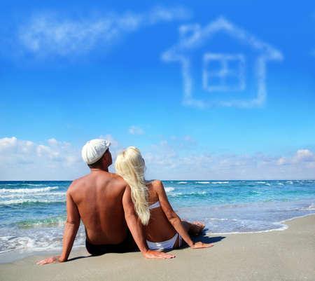 젊은 부부는 자신의 가정 개념에 대해 꿈을 바다 모래 해변에