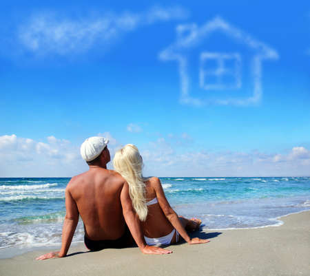 young couple on sea sand beach dreaming about the own home concept