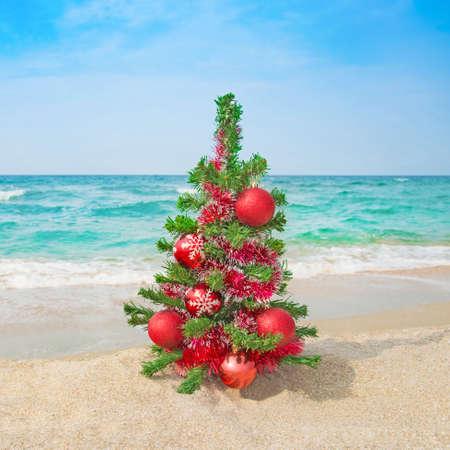 바다 해변에 빨간색 장식 된 크리스마스 트리. 크리스마스 휴가 개념.
