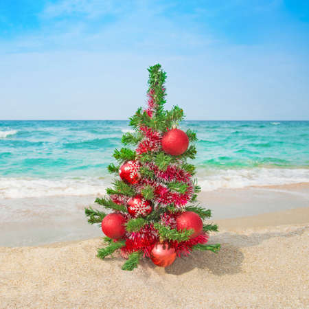 Christmas tree with red decorations on the sea beach. Christmas vacation concept.