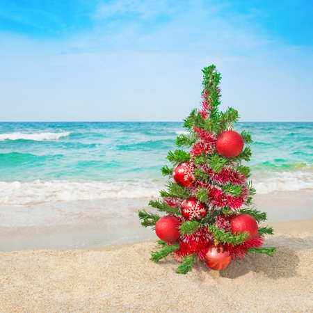 바다 해변에 빨간색 장식을 크리스마스 트리입니다. 크리스마스 휴가 개념.