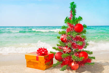 traditional christmas: Christmas tree and golden gift with big red bow on the sea sandy beach. Christmas vacation concept.