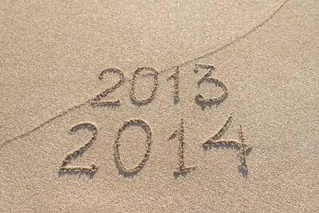New Year 2014 season is coming concept - inscription 2013 and 2014 on a beach sand photo
