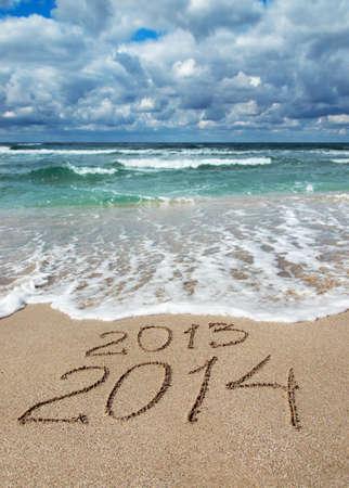Feliz A�o Nuevo 2014 a lavar a�o 2013 concepto en la playa de arena de mar photo