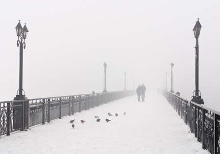 Bridge city landscape in foggy snowy winter day - walking couple, lanterns and doves flock - Ukraine, Donetsk photo