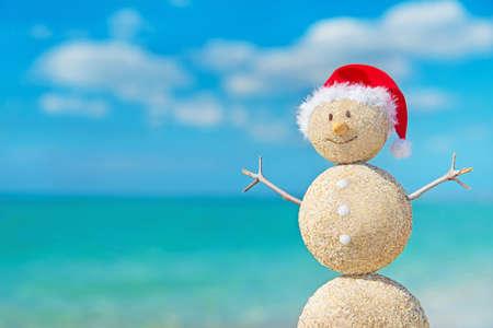 빨간색 산타 모자에 웃는 모래 눈사람. 연말 연시와 크리스마스 카드를위한 휴일 개념입니다.