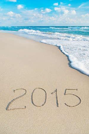 inscription 2015 on sea sand beach with the sun rays against wave foam and sky - vacation concept