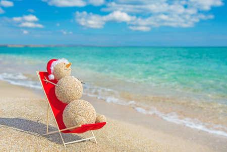 해변 라운지에서 일광욕 빨간 산타 모자에서 샌 디 눈사람. 새 해와 크리스마스 카드에 대 한 휴일 개념.