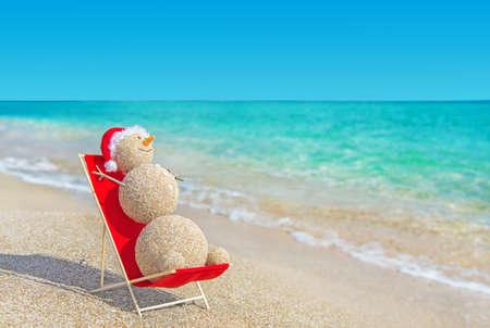 해변 라운지에서 빨간 산타 모자 일광욕에 모래 눈사람. 연말 연시와 크리스마스 카드를위한 휴일 개념. 스톡 콘텐츠 - 24917244