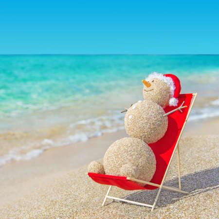 해변 라운지에서 빨간 산타 모자 일광욕에 모래 눈사람. 연말 연시와 크리스마스 카드를위한 휴일 개념입니다.