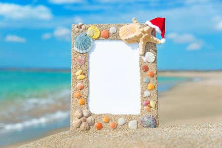 cushion sea star: Sea shells frame with christmas hat against sea sand beach