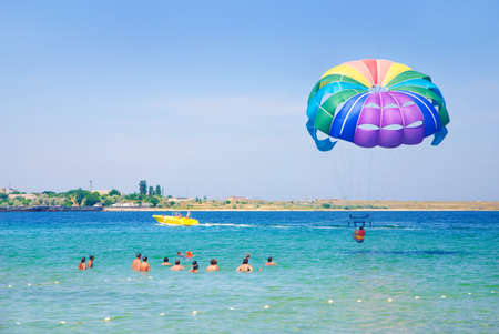 parasailing: colorful paragliding in the clear sky above the sea Stock Photo