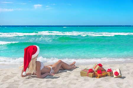 비키니, 빨간 크리스마스 모자와 바다 해변에서 많은 선물 상자에서 아름 다운 금발 여자. 뜨거운 국가 개념에 새 해 휴일 스톡 콘텐츠