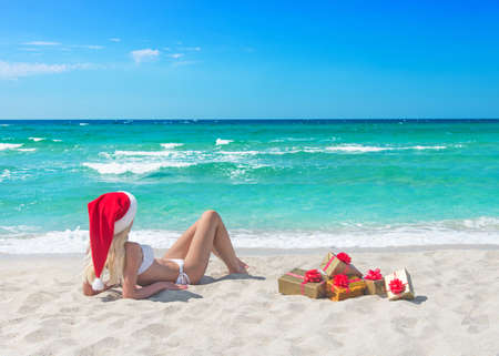 Beautiful blonde woman in bikini, red christmas hat and many gift boxes on sea beach. New year holidays in hot countries concept