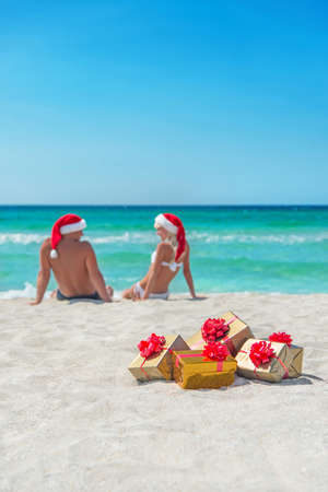 Young couple in santa hats at sea sand beach with christmas packed  golden gifts photo