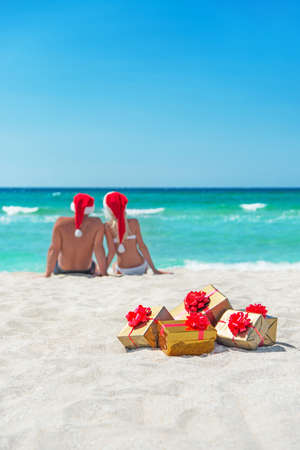 Young couple in santa hats at sea sand beach with christmas packed  golden gifts